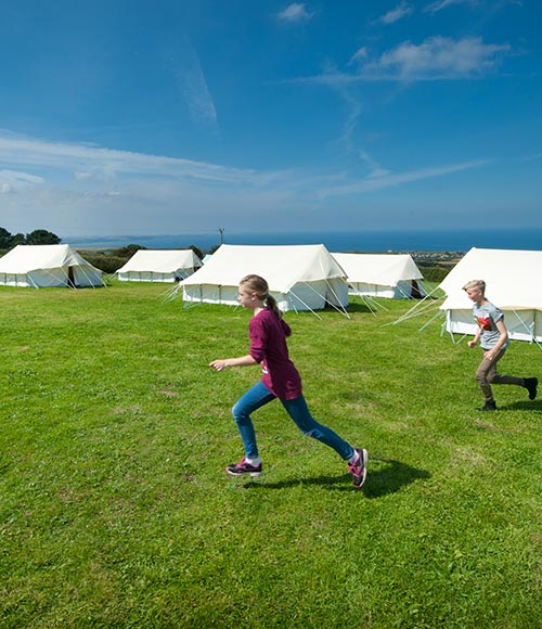 Girl running across the fields with camping tents in the background
